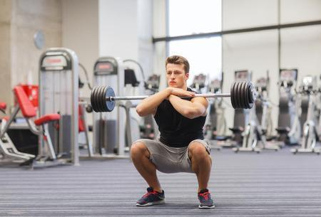 37674319 - sport, bodybuilding, lifestyle and people concept - young man with barbell doing squats in gym