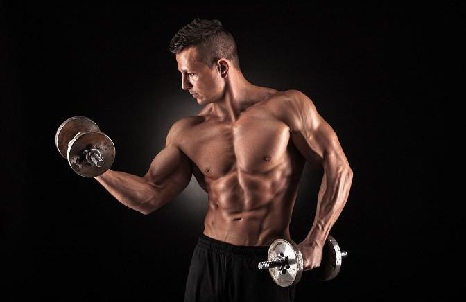 40755023 - handsome power athletic man bodybuilder doing exercises with dumbbell. fitness muscular body on dark background.