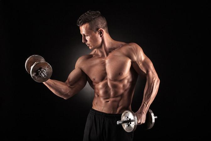 40755023 - handsome power athletic man bodybuilder doing exercises with dumbbell. fitness muscular body on dark background.