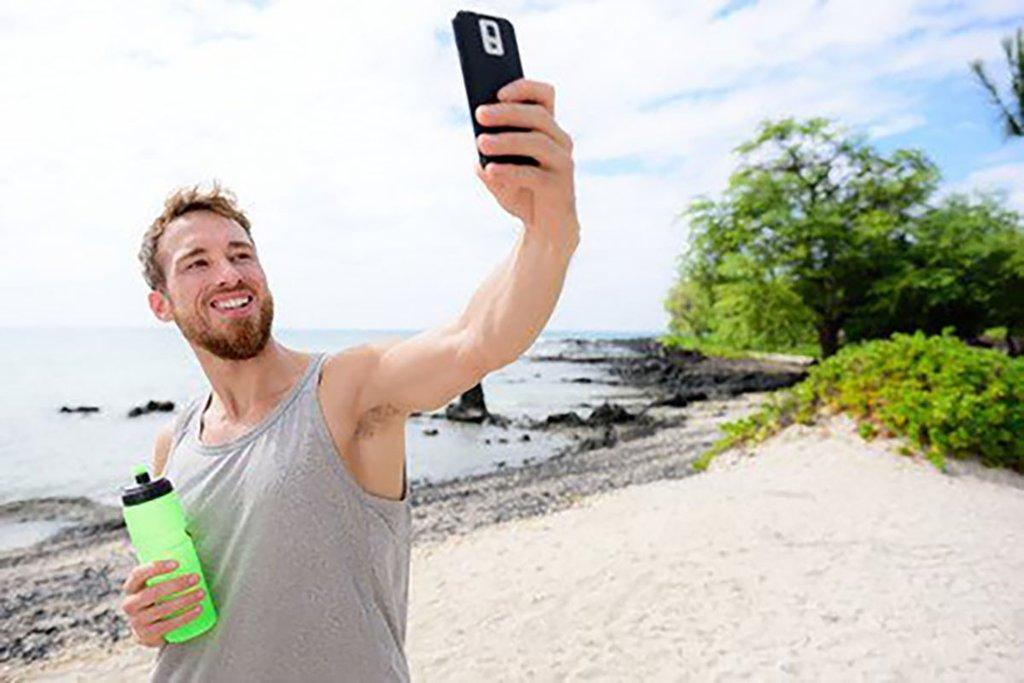 53759027 - fitness man taking selfie of himself after workout. good looking young adult taking a self-portrait picture with his smartphone camera after exercising on a beach during summer vacation travel.