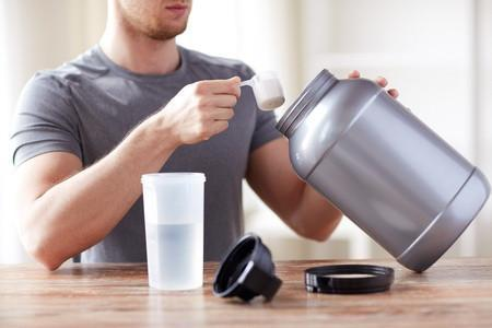 54776175 - sport, fitness, healthy lifestyle and people concept - close up of man with jar and bottle preparing protein shake
